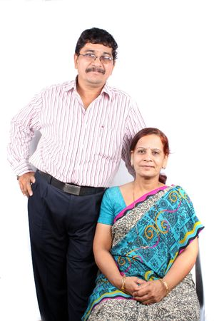 A portrait of a East Indian middle-aged couple from the Marwadi community, isolated on a white background.