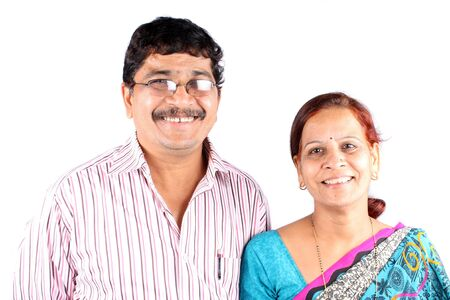 A portrait of a cute smiling middle-aged East Indian couple from the marwadi community, on white studio background.