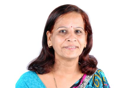 A portrait of a traditional middle-aged Indian woman from the Marwadi community in a sari, on white studio background. photo