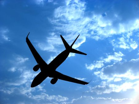 A background with a view of an airplane silhouette against the backdrop of a blue sky with little white clouds.