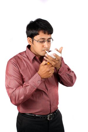 cigarette lighter: An Indian businessman lighting a cigarette, isolated on white studio background.