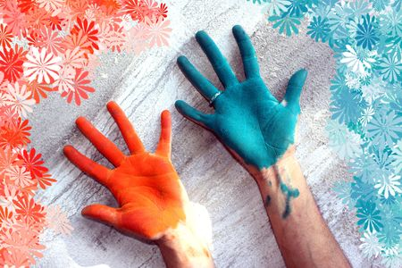 Hands colored with Holi festival colors, with a floral pattern around.