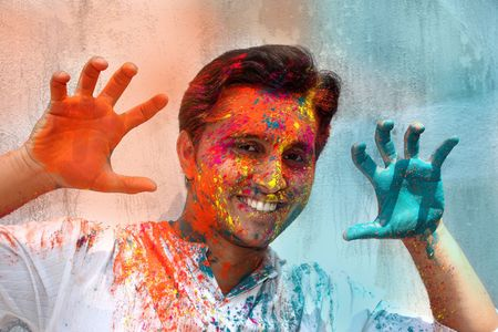 A young Indian guy having fun in Holi festival. photo