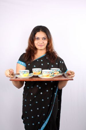 A traditional young Indian woman getting tea in a wooden serving tray.