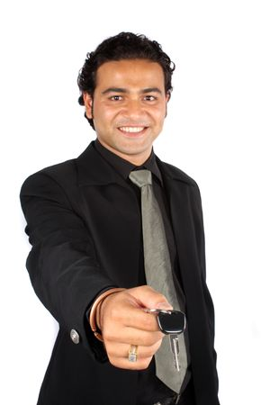 A young Indian businessman handing over the keys of a new car to a customer, isolated on white studio background.