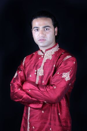 kurta: A portrait of a handsome Indian man in a traditional attire of a groom, on black studio background. Stock Photo