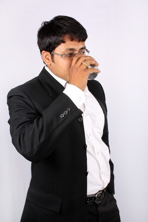 office break: Un empresario indio, el consumo de caf� durante el descanso de la Oficina, sobre fondo blanco de estudio. Foto de archivo