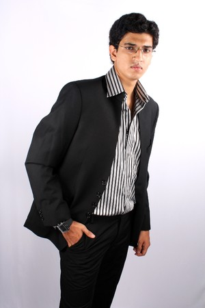 A young Indian business executive wearing glasses, on white studio background.