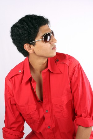 red shirt: A portrait of a handsome Indian teenager, on white studio background. Stock Photo