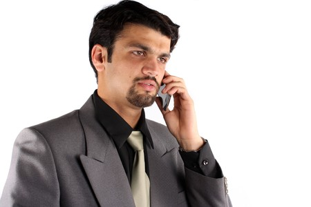 A young Indian businessman talking on his cellphone, on white studio background. photo