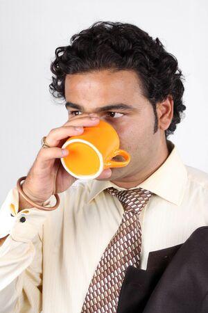 office break: Un empresario indio bebiendo caf� en una taza de naranja, durante un descanso de la Oficina.