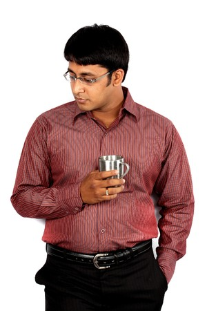 tensed: A tensed Indian guyexecutive holding a coffee cup, leaning against a white wall. Stock Photo