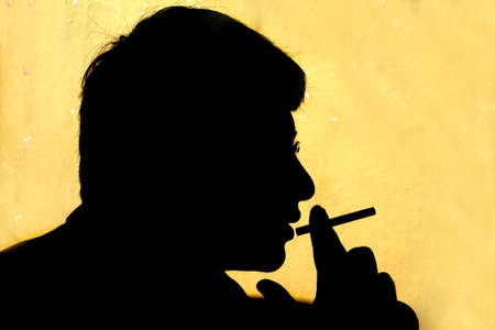 A metaphorical image of a silhouette of a guy smoking. The silhouette represents the hazard of smoking. photo