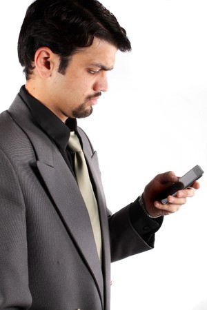 An Indian businessman checking his cellphone, on white studio background. photo