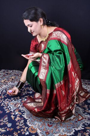 An Indian lady traditionally arranging earthen lamps on the floor, on the occassion of Diwali festival in India