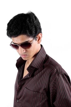 Un retrato de un adolescente indio guapo llevando gafas de sol, sobre fondo blanco de estudio.