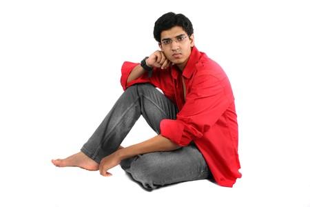 Un chico joven adolescente indio, sobre fondo blanco de estudio.
