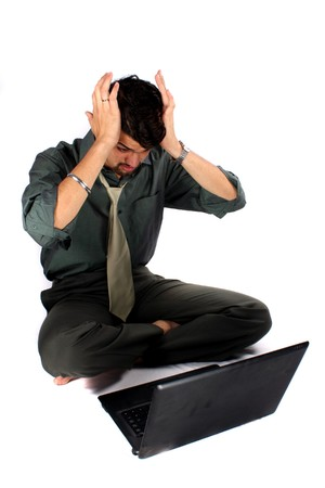 An expression of an Indian business executive after making a mistake on his laptop computer. Also metaphorical as expression after seeing business loss, on white studio background. photo