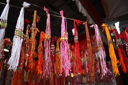 Colorful rakhis used in the traditional Indian festival, hung for sale at a street-side shop.