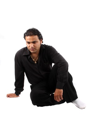 A depressed Indian guy sitting on the floor, on white studio background. photo