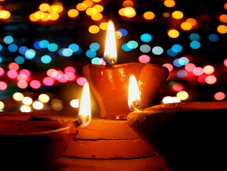 Traditional lamps lit in front of colorful lighting, during Diwali festival in India. photo