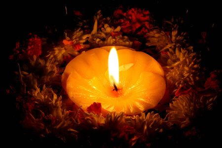 A holy candle surrounded by flowers for traditional Diwali festival rituals.