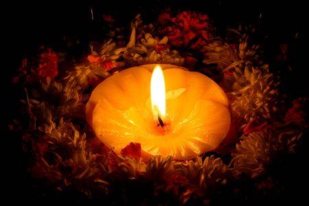 rituales: Una vela Santa rodeada de flores para los rituales de festivales de Diwali tradicionales.
