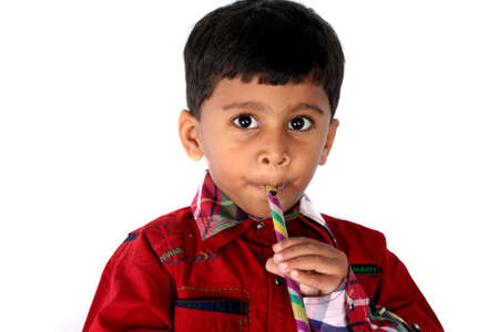 A cute Indian kid playing a toy flute, isolated on white studio background. Stock Photo - 8904082