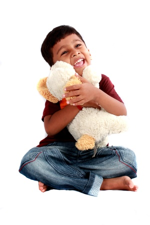 A cute Indian boy with a soft toy dog, on white studio background.