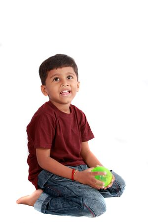 An Indian boy sitting with a ball, on white studio background.