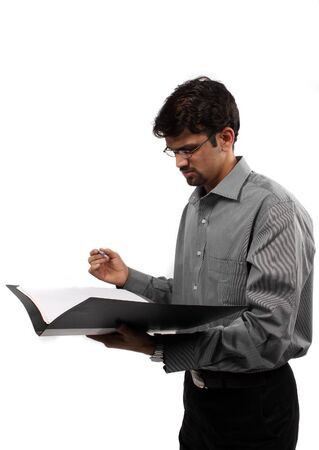 An Indian business executive signing documents in a file, on white studio background. Stock Photo - 9383488