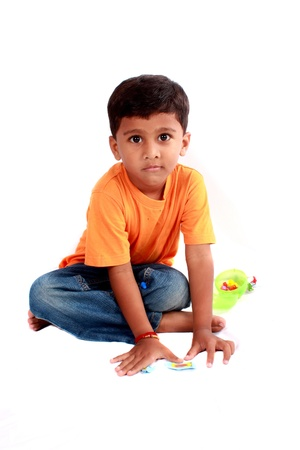 A cute Indian boy sitting on the floor, on white studio background.