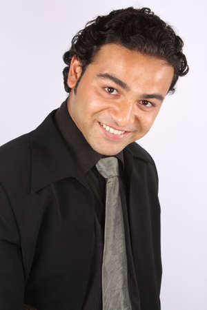 A young Indian businessman in a happy mood, on white studio background. photo