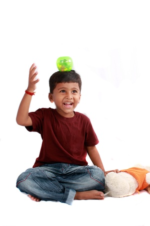 A playful Indian boy balancing a ball on his head, on white studio background.
