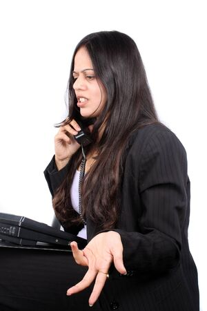 An Indian businesswoman irritated over a telephonic conversation, on white studio background. photo