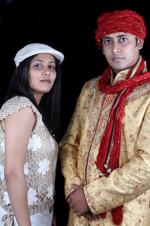 Two Indians wearing clothes of diverse cultures, on black studio background. photo