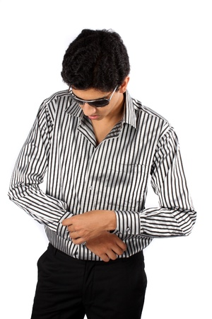 A handsome young Indian guy dressing up, on white studio background. photo