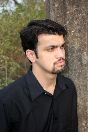 heartbroken: A portrait of a heartbroken Indian man in a sad mood, leaning on a tree. Stock Photo