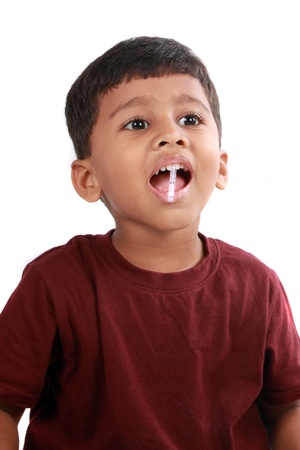 A little boy trying to bite a plastic clip which can get stuck in his throat if swallowed by mistake. photo