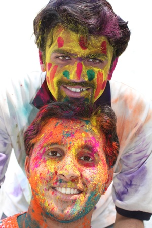 Two young guys with their faces tradiitionally painted in colorful powders, on the occasion of holi festival in India. photo