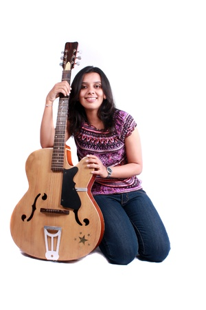 A beautiful female Indian guitarist with an acoustic guitar.