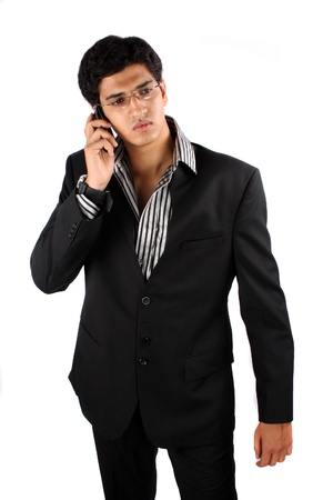 A young Indian businessman talking on the phone, on white studio background. Stock Photo