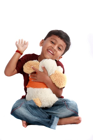 A cute Indian boy happy with his stuffed toy, on white studio background. photo