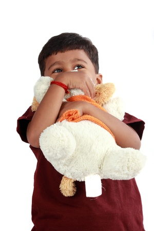 An Indian boy hugging his soft teddy bear, on white studio background. photo