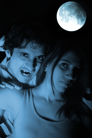 Horrific young Vampire lovers under the blue full moon. Stock Photo
