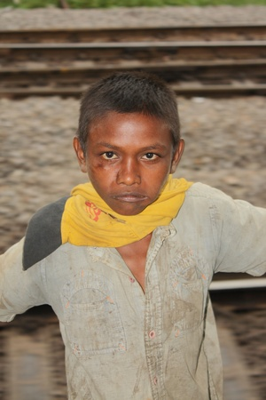 A young beggar boy standing dangerously at the door of a fast moving train, in India.