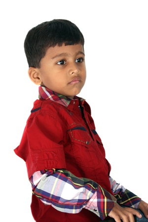 A portrait of an Indian boy in a unhappy mood, on white studio background. photo