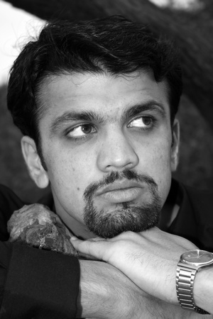 A black & white portrait of a young worried Indian man. photo