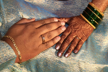 wedding ring hands: Hands with exchanged rings and placed together in a ritual, in an Indian wedding. Stock Photo