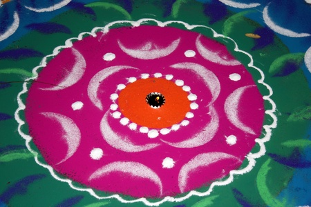 A lamp lit in between a traditional design made of colorful powder called Rangoli, on the occassion of Diwali festival in India.